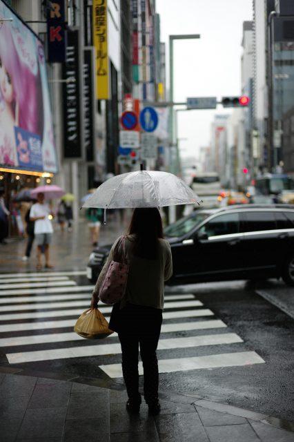 woman with umbrella crossing road